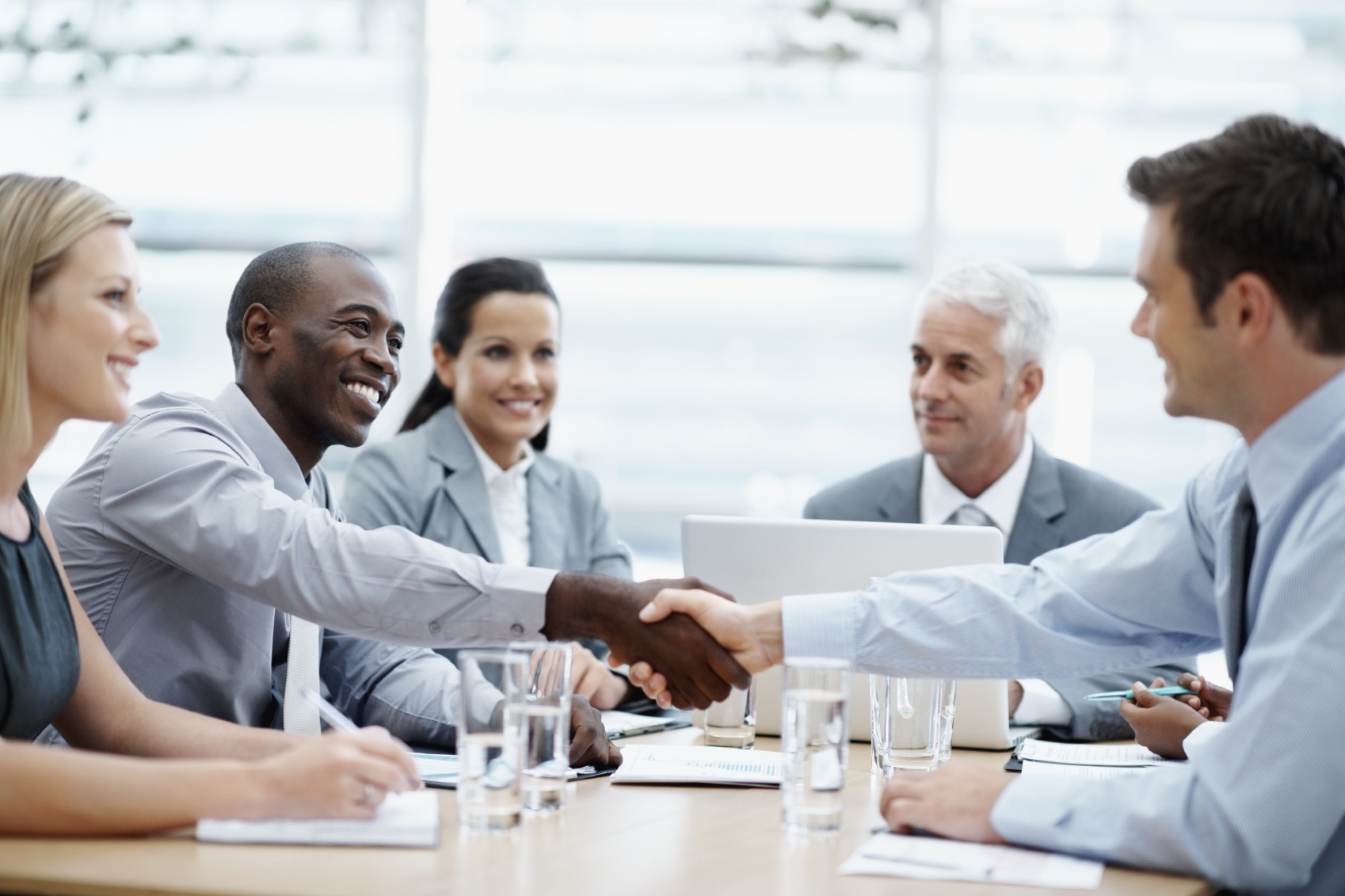 Young business men shaking hands happily in the conference room